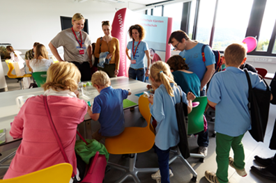 Pupils and their parents  experimenting with great enthusiasm. In the background pre- and in-service teachers.